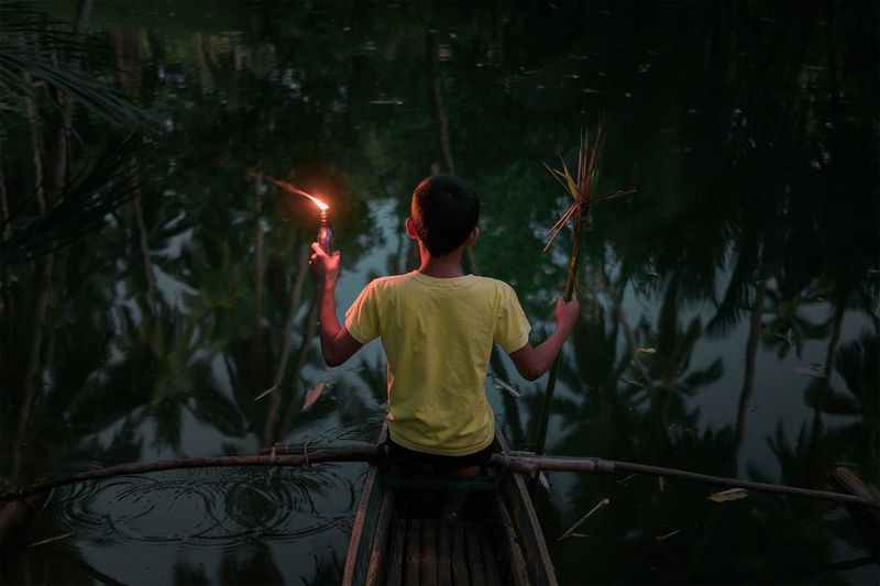 Rear view of boy on kayak in the night