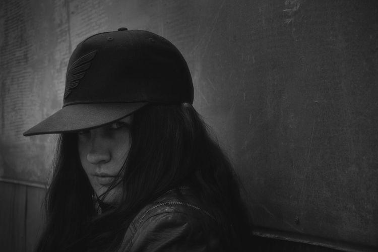 Portrait of woman wearing hat against wall