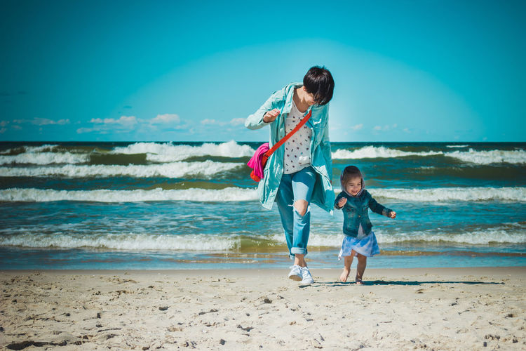 Mother and daughter walking at beach against blue sky
