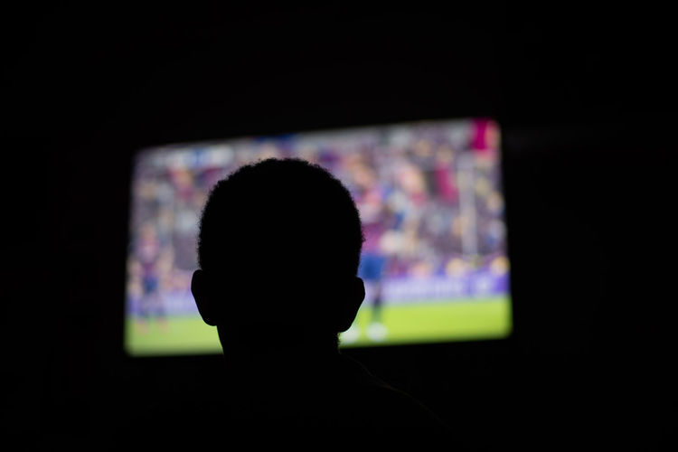 Person watching television in dark room