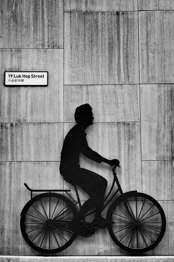Side view of man riding bicycle sign on wall