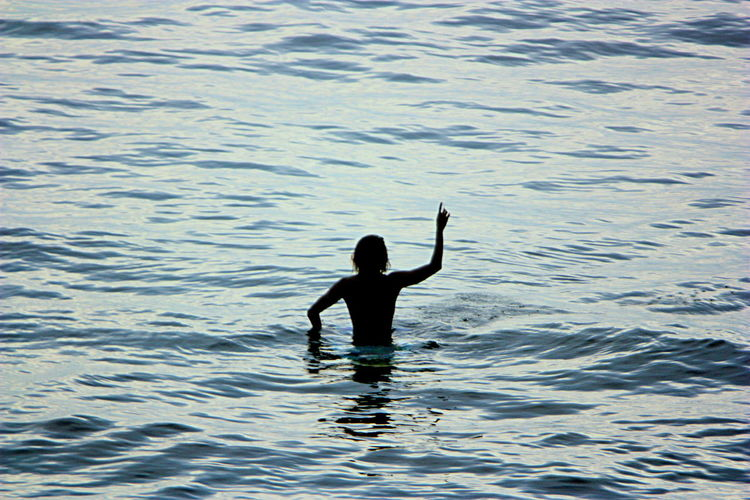 Rear View Of Silhouette Man With Arm Raised At Sea