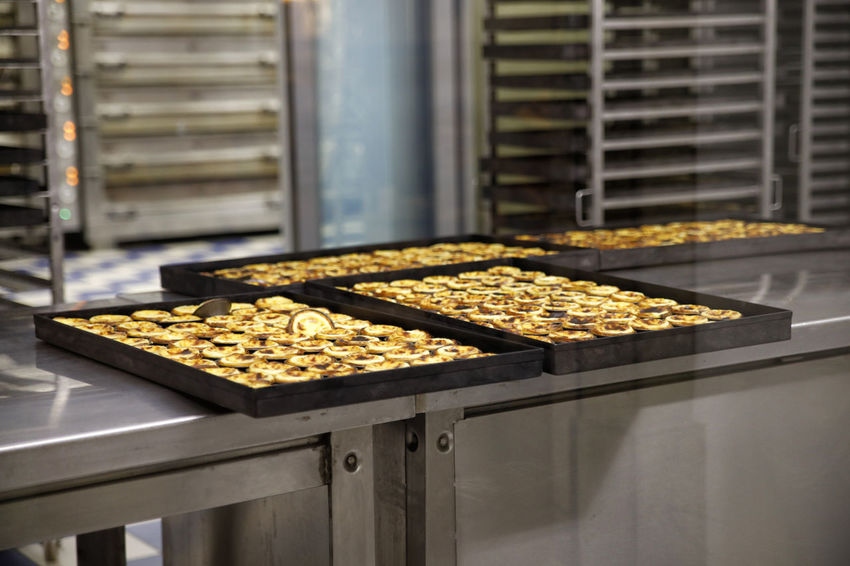 pastel de nata on patisseire Belém Abundance Commercial Kitchen Day Factory Food Food And Drink Food And Drink Industry Freshness Healthy Eating Indoors  Industry Nata No People Oven Pastel De Nata Patisserie Preparation  Production Line Stove Traditional