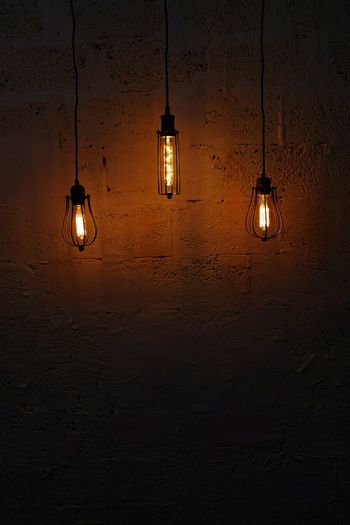 Low angle view of light bulb hanging against wall