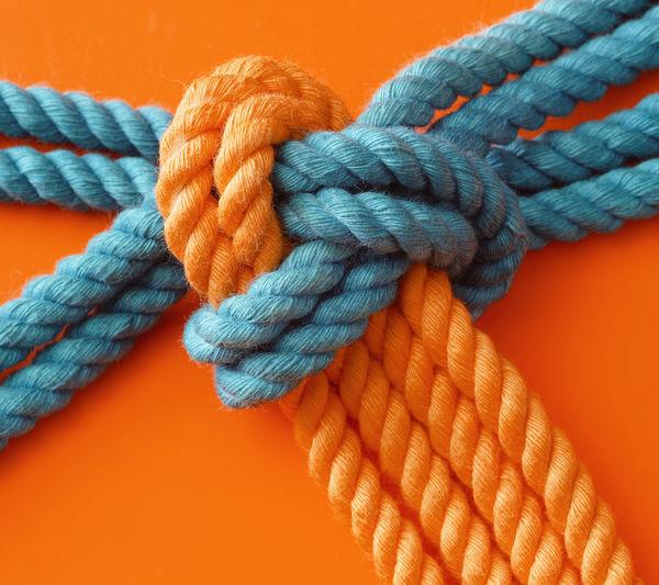 Close-Up Of Ropes Against Orange Background