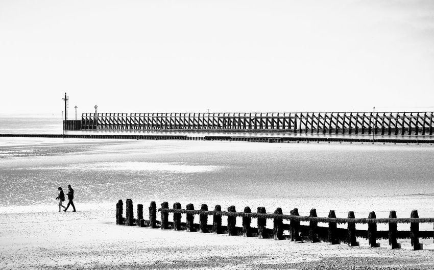 GROYNE AND BREAKWATER: The breakwater flanks the path of the River Arun where it joins the English Channel. Littlehampton, West Sussex. Breakwater Groyne Monochrome Chirascuro Architecture Beach Bridge Built Structure Clear Sky Connection Copy Space Day Horizon Horizon Over Water Land Men Nature Outdoors Promenade Railing Real People Sea Sky Two People Walking Water Low Tide