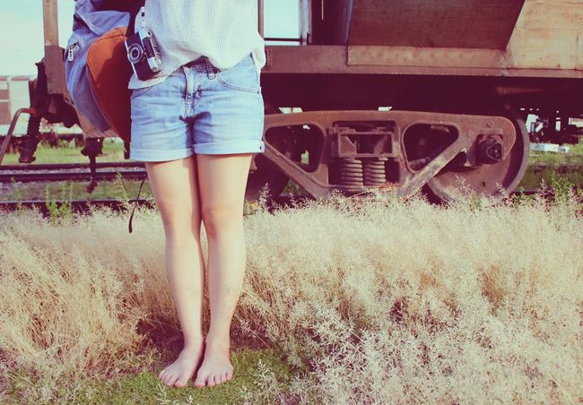Young woman with film camera and bag stands barefoot on green grasses in front of old train, vintage filter Hipster Traveler Traveling Travel Barefoot Vintage Train Grasses Film Camera Bag Woman Transportation Transport Previous Past Teen Young Youth Outdoor Activity Photography Lifestyle