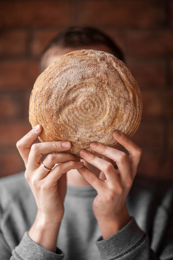 The guy holds round bread in front of his face. Unrecognizable person. Food Food And Drink Lifestyles Real People Lifestyle One Person Holding Indoors  Hand Human Body Part Headshot Adult Human Hand Portrait Close-up Focus On Foreground Bread Front View Studio Shot Freshness Obscured Face Clothing Finger Unrecognizable Person Capture Tomorrow