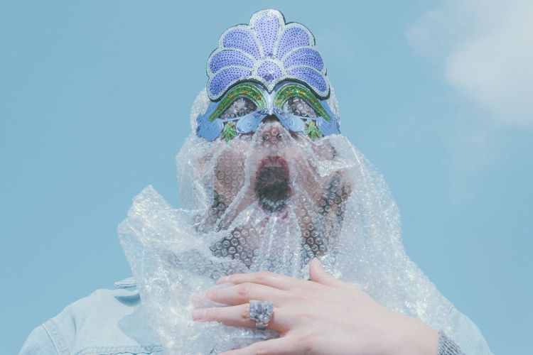 Low angle view of woman wearing mask and bubble wrap standing against sky