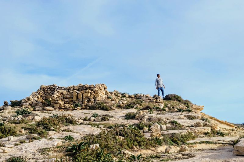Teenage boy standing on rock formation against sky