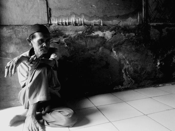 Senior man sitting on tiled floor at home