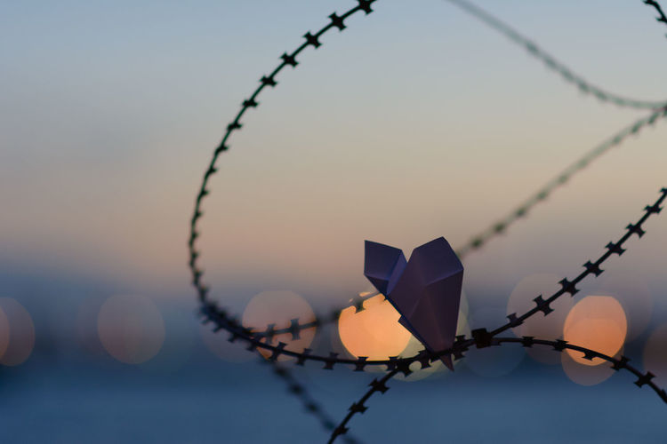 Close-up of barbed wire fence against sky during sunset