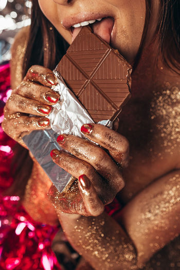 Midsection of woman eating chocolate
