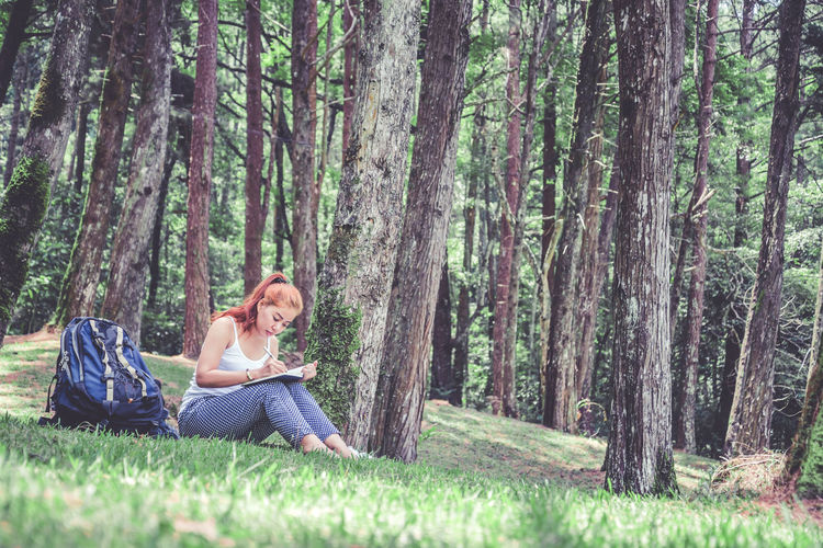 Woman siting on grass and writing in book in forest