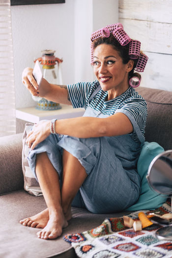 Woman with hair curlers taking selfie while sitting on sofa at home