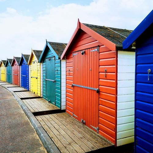 Multi colored huts on beach by building against sky