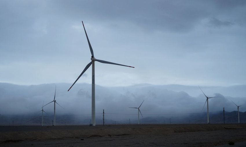 View of wind farm by foggy mountains
