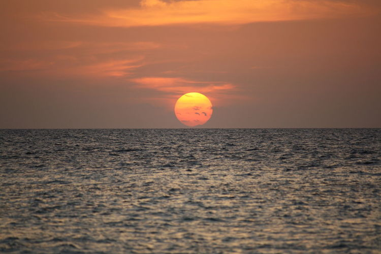 Sunset with a full sun at the sea