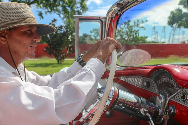 Cuban in a hat driving a vintage car, Cuba, Varadero Mode Of Transportation Day Car Transportation Land Vehicle Outdoors Real People One Person Men Adult Motor Vehicle Senior Adult Holding Sitting Mature Men Hat Cuban Windshield Clothing Lifestyles Cuba Varadero Cuba. Varadero Belair Hat Sitting Transportation Adult