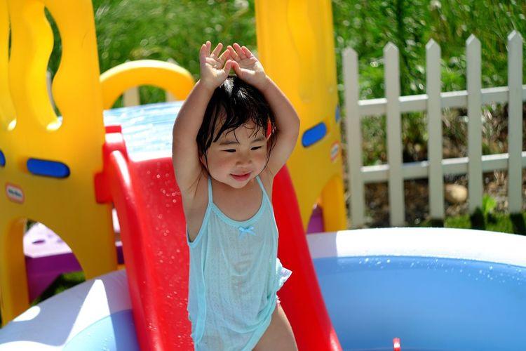 Girl Sliding On Water Slide In Wading Pool