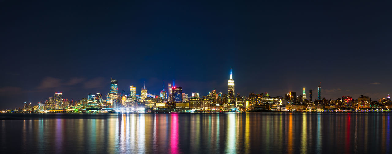 Panoramic view of illuminated cityscape by river at night