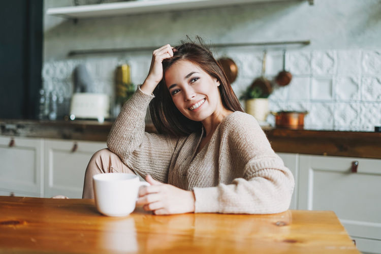 Portrait of smiling young woman with coffee cup on table
