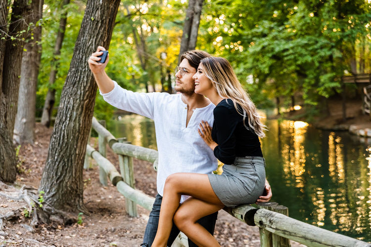 Full length of woman using mobile phone while sitting on tree