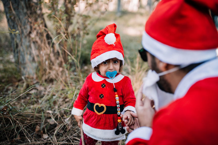 Portrait of cute baby girl wearing santa costume looking at father