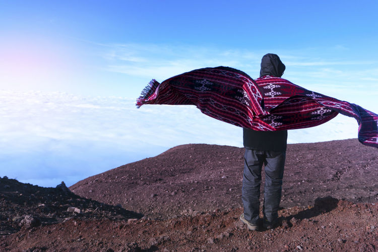 summit with my woven cloth Kain Nusantara Tenun INDONESIA Woven Pattern Woven Mountain Sarong Summit Standing Women Full Length Rear View Happiness Sky Mountain Range Warm Clothing Hiker Mountain Peak