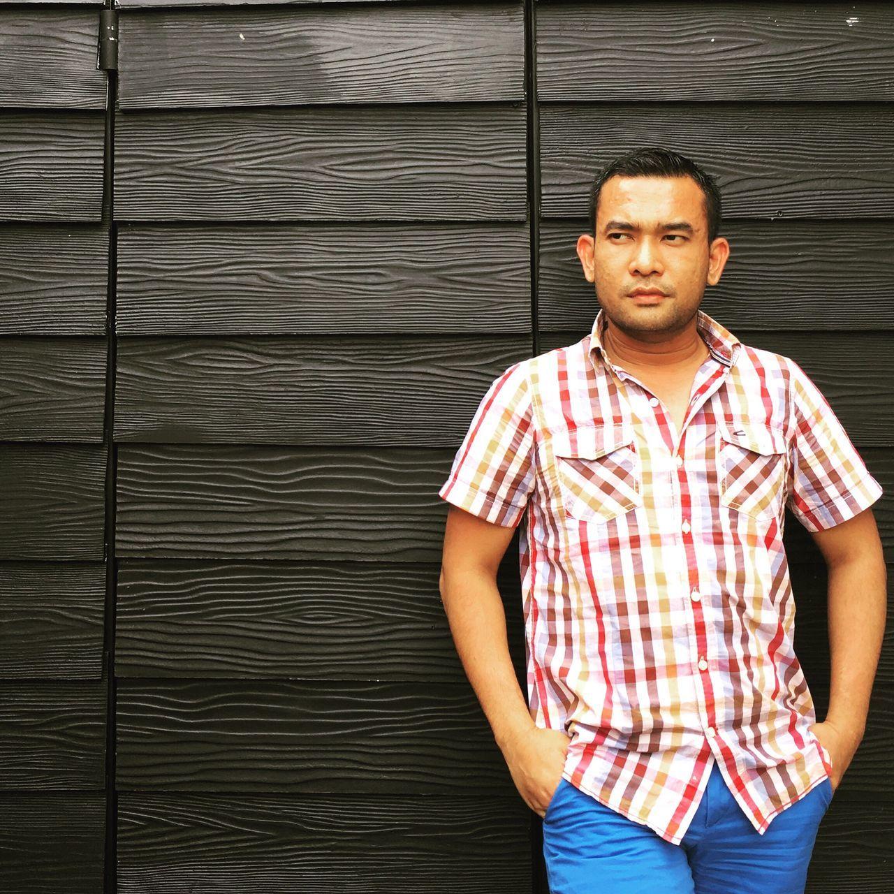 Man Standing Against Wooden Door