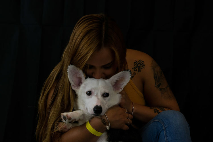 Woman kissing dog against black background