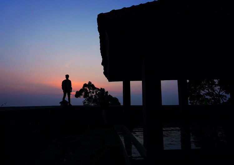 Silhouette man standing on retaining wall against sky during sunset
