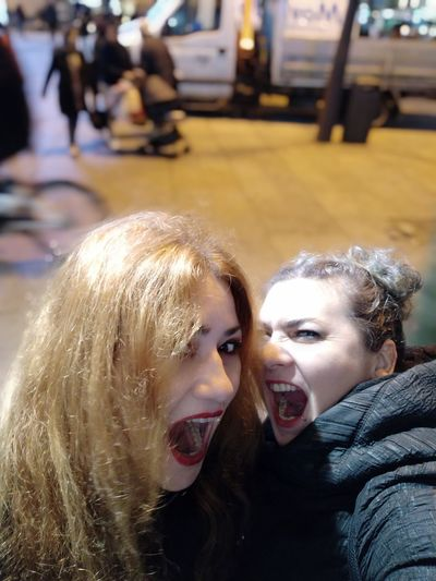 Portrait of cheerful friends in city at night
