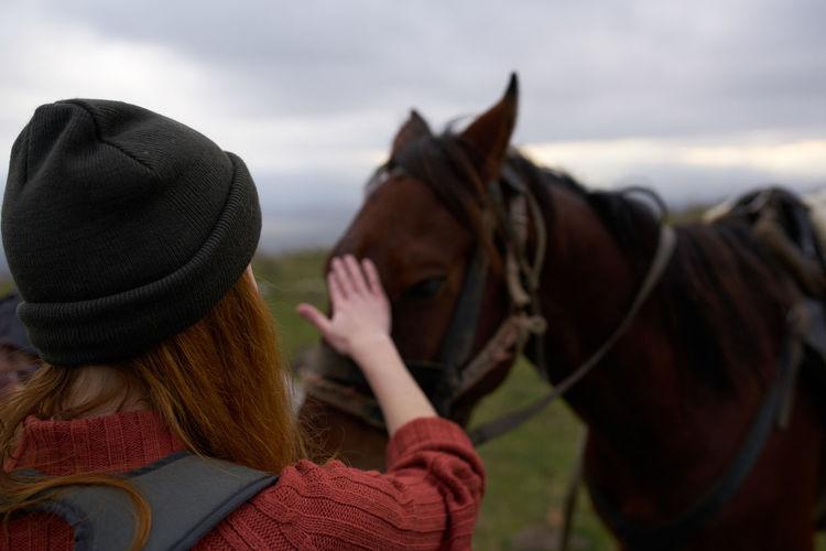 Rear view of women wearing hat against sky