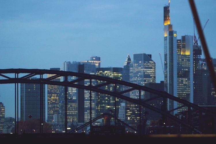Illuminated bridge and buildings against sky in city
