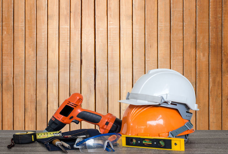 Construction tools on table against wooden wall