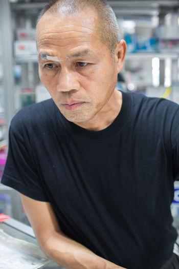 Close-up of thoughtful owner with bandage standing at shop