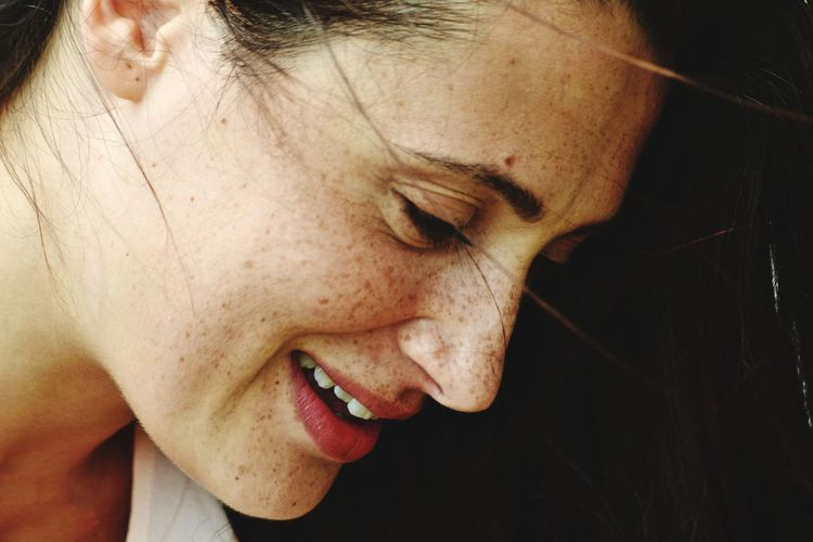 Close-up of smiling young woman looking down