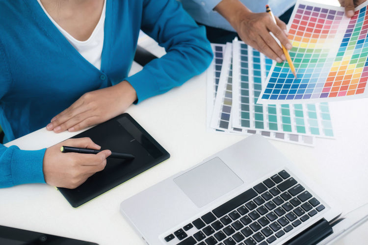Close-up of business colleagues choosing color swatch while working in office