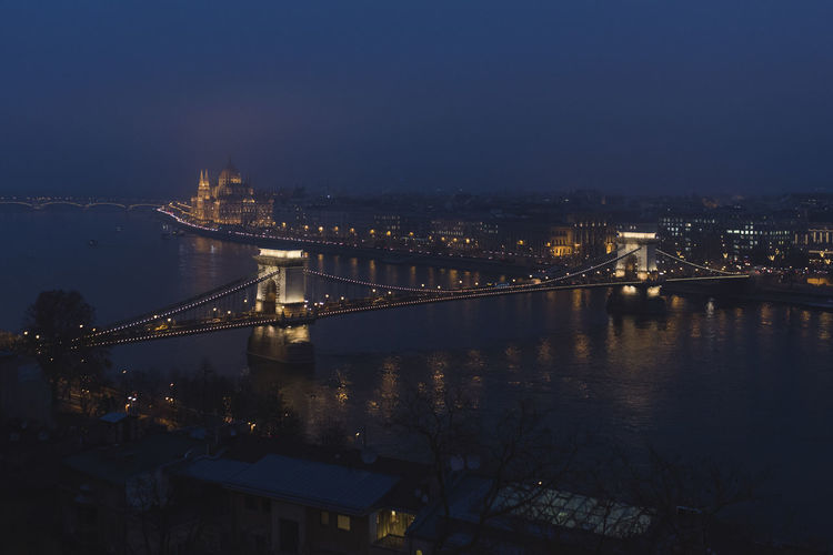 Nighttime skyline of the historic city of Budapest on a foggy Cathedral and Chain Bridge crossing the Danube River Architecture Bridge Bridge - Man Made Structure Building Exterior Built Structure Chain Bridge City Connection Illuminated Nature Night No People River Sky Suspension Bridge Transportation Travel Destinations Water