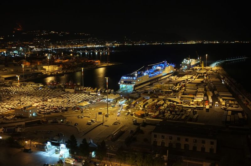 High angle view of illuminated buildings by sea against sky at night