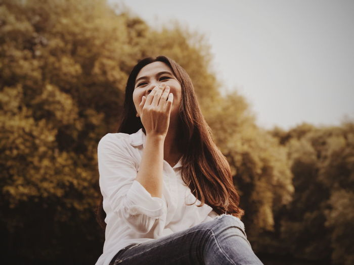 Low Angle View Of Woman With Hands Covering Mouth Against Trees