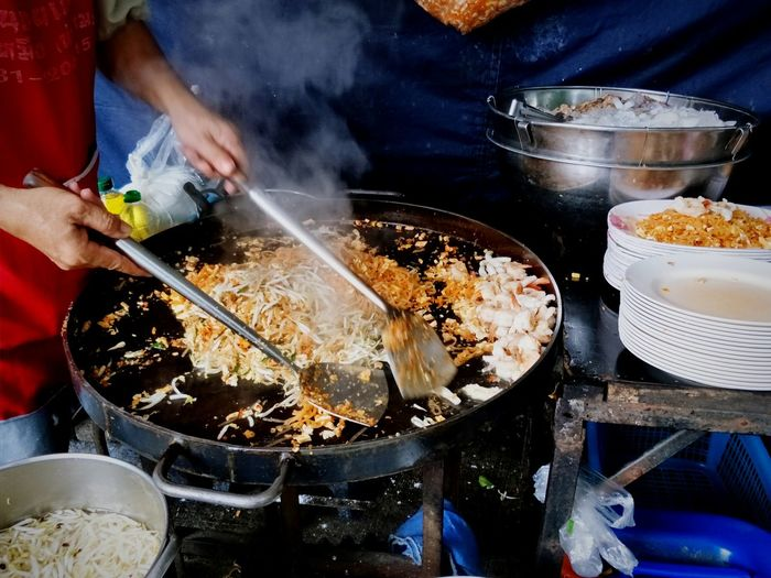 Midsection of person preparing food on barbecue grill