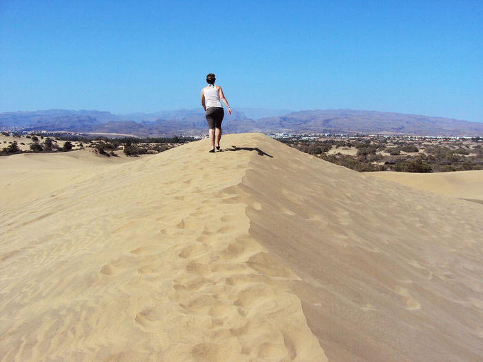 Rear view full length of tourist walking on sand dune at grand canary