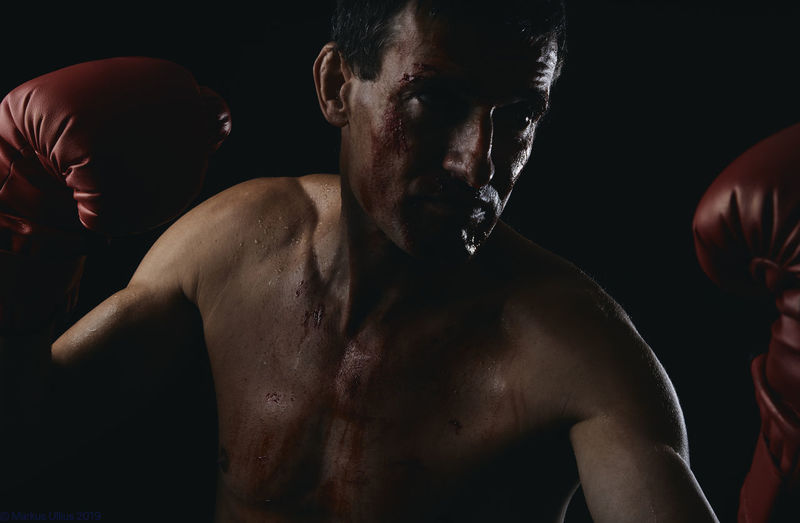 shirtless man with boxing glove standing against black background