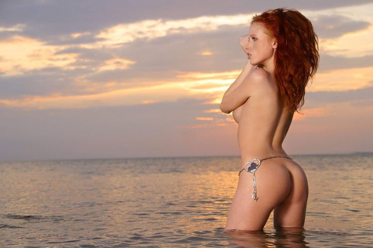 Young woman in bikini standing on beach against sky during sunset