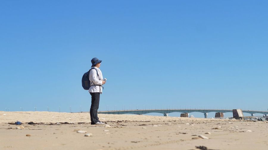 Side view full length of woman standing at sandy beach against clear blue sky