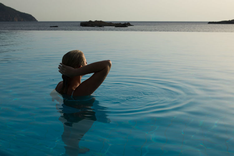 Woman in infinity pool by sea during sunset