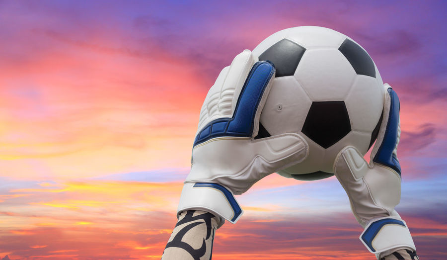 Cropped hands of goalie holding soccer ball against cloudy sky during sunset