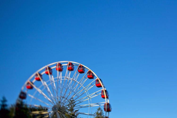 Low Angle View Of Ferris Wheel Against Clear Blue Sky During Sunny Day